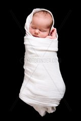 Baby Cocoon  Swaddled 15 days old newborn baby girl over black background