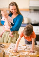 Young family in kitchen making gingerbread cookies