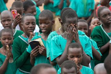 Bombo  Uganda - Betende Schueler beim Schulappell auf dem Schulhof der St. Joseph's Bombo mixed primary school.