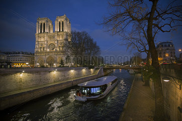 A pleasure boat moves past Notre Dame Cathedral on the Seine River at twilight  Paris  France