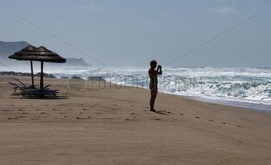 Sardinien  Italien  eine Frau am Strand der Costa Verde fotografiert die Wellen