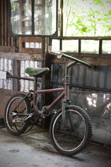 Neglected bicycle with broken chain in shed