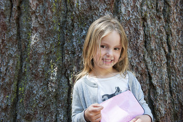 Girl leaning against tree trunk  smiling cheerfully