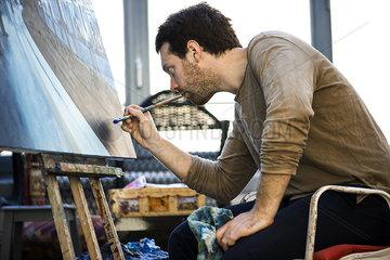 Artist working on oil painting in art studio