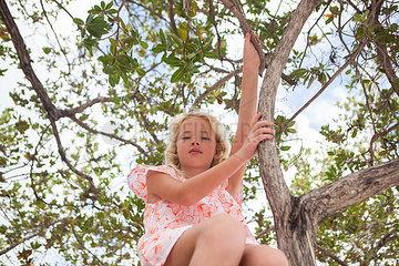Blondes Maedchen sitzt im Baum