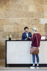 Woman text messaging during transaction with receptionist