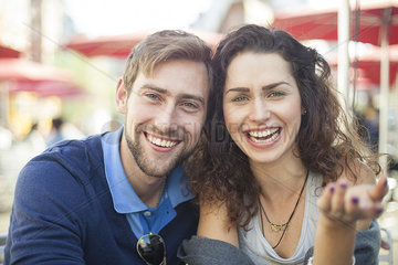 Young couple laughing together outdoors  portrait