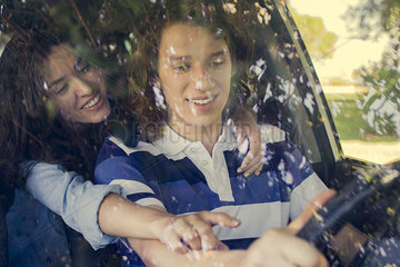 Young woman helping friend learn to drive