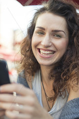 Young woman using smartphone  smiling  portrait