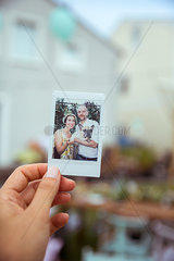 Frau haelt Polaroid-Foto in der Hand