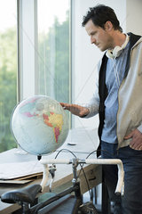 Man looking at globe