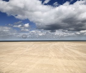Blowing sand in High wind on wide St Andrews West Sands beach with blue sky and white clouds and North Sea at St Andrews Fife Scotland UK