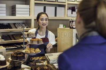 Young woman assisting customer in bakery