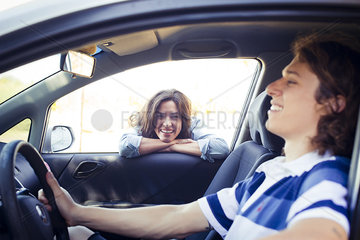 Woman looking into car window while man sitting in driver seat