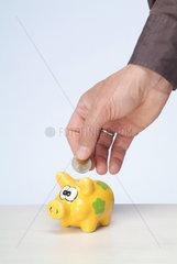 Hamburg  Deutschland  eine Maennerhand steckt einen Euro ins Sparschwein