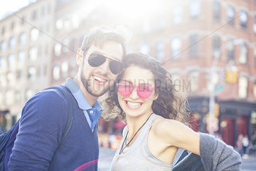 Young couple smiling together in urban setting  portrait