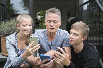 Vater und Kinder mit Smartphones