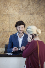 Friendly receptionist waiting to assist customer on cell phone