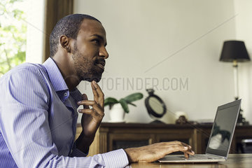 Man using laptop computer for online investment opportunities