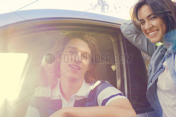 Woman standing next to man sitting in car