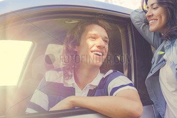 Woman talking to man sitting in car