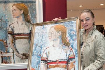 Berlin  Deutschland  die ehemalige Eiskunstlaeuferin Gabriele Seyfert mit einem Protrait gemalt von Bert Heller