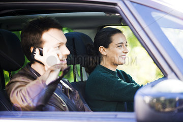Woman driving while passenger chats on phone
