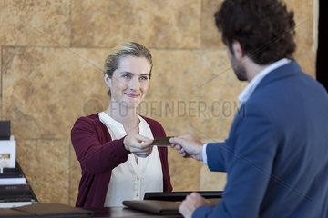 Friendly hotel receptionist taking customer's credit card