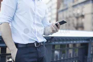 Businessman holding smartphone  mid section