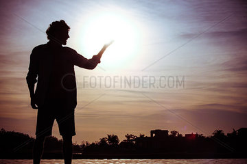 Man pretending to hold the sun at water's edge