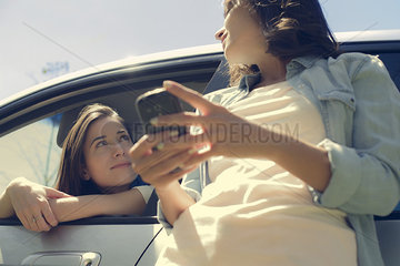Woman leaning out of window from driver seat and talking to friend