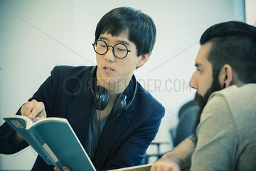Man discussing book on human rights with colleague