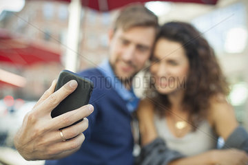 Man using smartphone to photgraph himself with his wife