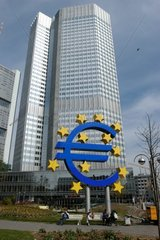 Parkbank mit Spaziergaengern und Eurozeichen vor EZB Bank