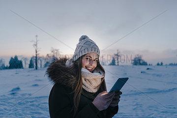 Junge Frau mit Tablet PC in Schneelandschaft