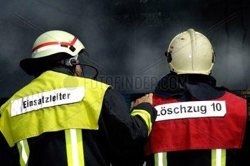 Zwei Feuerwehrleute vor einer Rauchwand