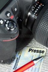 Kamera und Presseausweis auf einer Zeitungsseite Camera and press card on a newspaper