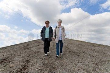 2 Frauen laufen nebeneinander auf einem Schotterweg bergab