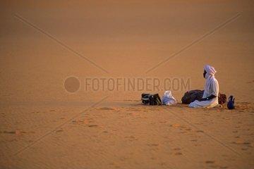 betender Moslem sitzt im Sand