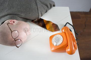 Junger Mann wartet auf einen Telefonanruf.