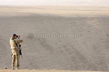 Mazar-e Sharif  Afghanistan  Bundeswehr-ISAF-Soldat auf Patrouille mit Fernglas