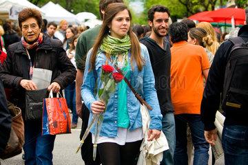 Barcelona  Spanien  eine junge Frau mit Rosen in der Menschenmenge am Sant Jordi Tag