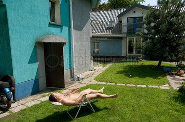 Breslau  Polen  ein Mann liegt vor seinem Haus auf einer Liege und sonnt sich