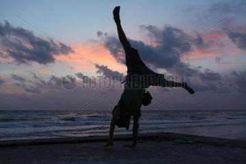 Pass A Grille  Vereinigte Staaten von Amerika  Silhouette  Junge schlaegt ein Rad bei Daemmerung am Strand