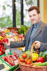 Mann kauft Gemuese im Biomarkt