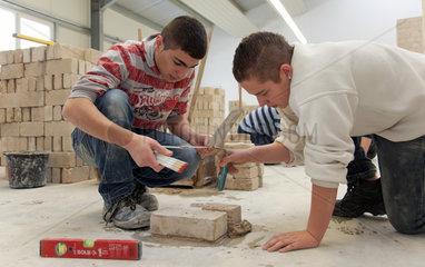 Berlin  Deutschland  Schuelerpraktikanten bei Mauerversuchen auf dem Lehrbauhof