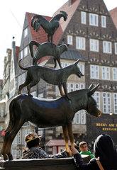 Bremen  Deutschland  Menschen umfassen die Vorderbeine des Esels der Bremer Stadtmusikanten