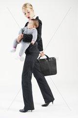 Businessfrau und Mutter mit Baby im Arm auf dem Weg zur Arbeit