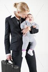 Businessfrau und Mutter mit lachendem Baby im Arm