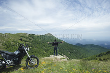 Man standing on top of rock with arms outstretched  rear view